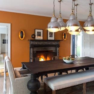 Ispirazione per una grande sala da pranzo tradizionale chiusa con pareti arancioni, pavimento in legno massello medio, camino classico e cornice del camino in pietra
