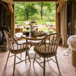 Immagine di una sala da pranzo aperta verso il soggiorno rustica di medie dimensioni con pareti bianche, parquet chiaro, stufa a legna, cornice del camino in legno e pavimento beige