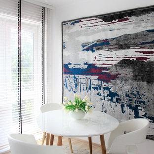 Immagine di una sala da pranzo minimalista chiusa e di medie dimensioni con pareti bianche, pavimento in laminato, nessun camino e pavimento marrone