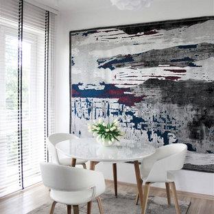 Cette image montre une petit salle à manger minimaliste fermée avec un mur blanc, sol en stratifié, aucune cheminée et un sol orange.
