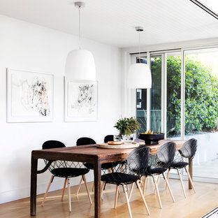 Design ideas for a small contemporary open plan dining in Sydney with white walls and light hardwood floors.