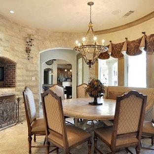 Стильный дизайн: отдельная столовая среднего размера в викторианском стиле с бежевыми стенами, полом из травертина, стандартным камином и фасадом камина из камня - последний тренд