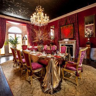 Ispirazione per una grande sala da pranzo vittoriana chiusa con pareti rosse, parquet scuro, camino classico, cornice del camino in cemento e pavimento marrone