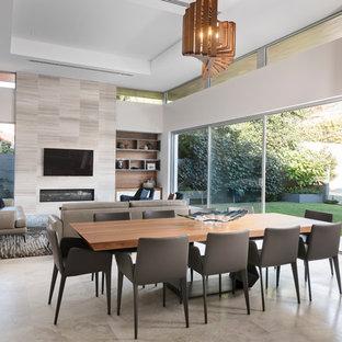 Пример оригинального дизайна: огромная гостиная-столовая в современном стиле с серыми стенами, стандартным камином, фасадом камина из плитки, серым полом и полом из известняка