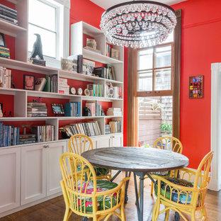 Imagen de comedor ecléctico, de tamaño medio, sin chimenea, con paredes rojas y suelo de madera en tonos medios