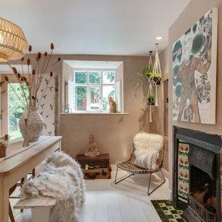 チェシャーの小さいエクレクティックスタイルのおしゃれなダイニング (朝食スペース、ピンクの壁、塗装フローリング、標準型暖炉、漆喰の暖炉まわり、白い床) の写真
