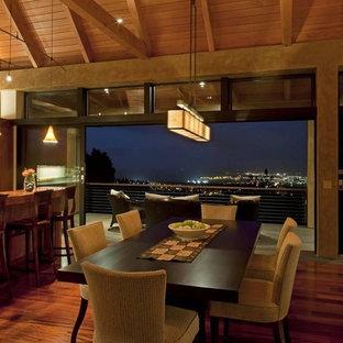 Cette photo montre une grande salle à manger ouverte sur la cuisine exotique avec un mur beige, un sol en bois foncé, aucune cheminée et un sol marron.
