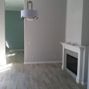 Foto di una piccola sala da pranzo aperta verso la cucina contemporanea con pareti grigie, pavimento in gres porcellanato, camino classico e cornice del camino piastrellata