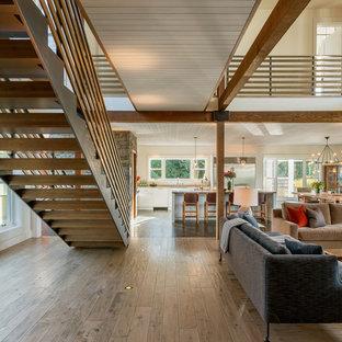 Ejemplo de comedor de estilo de casa de campo, grande, abierto, con paredes beige, suelo de madera clara, chimeneas suspendidas, marco de chimenea de piedra y suelo marrón