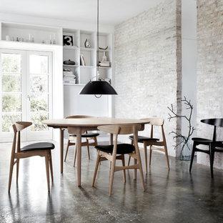 Immagine di una sala da pranzo industriale con pavimento in cemento