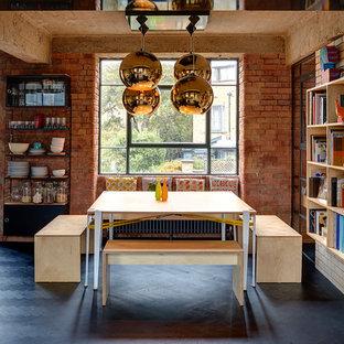 Immagine di una sala da pranzo industriale con pareti rosse, parquet scuro e pavimento nero