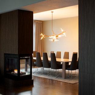Bild på en stor funkis matplats med öppen planlösning, med beige väggar, mellanmörkt trägolv, en dubbelsidig öppen spis och en spiselkrans i trä
