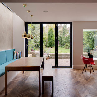 Great room - contemporary medium tone wood floor great room idea in London with white walls