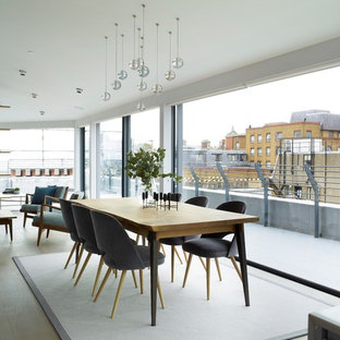 Design ideas for a contemporary open plan dining room in London with grey floors.