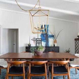 Immagine di una sala da pranzo aperta verso la cucina minimalista di medie dimensioni con pareti bianche, parquet scuro, camino classico e cornice del camino piastrellata