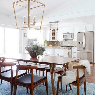 Modelo de comedor de cocina vintage, de tamaño medio, con paredes blancas, suelo de madera oscura, chimenea tradicional y marco de chimenea de baldosas y/o azulejos