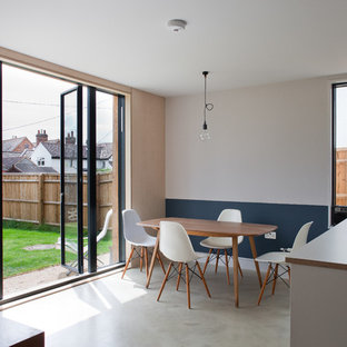 Photo of a medium sized scandi open plan dining room in Buckinghamshire with concrete flooring, grey floors and multi-coloured walls.