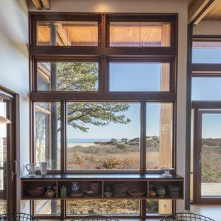 Ejemplo de comedor vintage, de tamaño medio, abierto, con paredes blancas, suelo de madera clara, chimenea de doble cara, marco de chimenea de hormigón y suelo marrón
