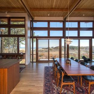 Foto di una sala da pranzo aperta verso il soggiorno moderna di medie dimensioni con pareti bianche, parquet chiaro, camino bifacciale, cornice del camino in cemento e pavimento marrone