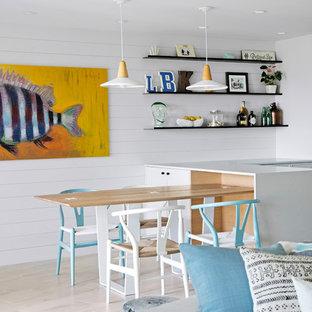 Ejemplo de comedor de cocina costero, pequeño, sin chimenea, con paredes blancas, suelo de baldosas de cerámica y suelo beige