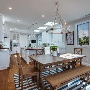 Immagine di una grande sala da pranzo aperta verso la cucina stile marinaro con pareti beige, pavimento in legno massello medio, nessun camino e pavimento marrone