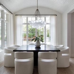 Foto di un'ampia sala da pranzo classica chiusa con pareti bianche, pavimento in legno massello medio, pavimento marrone, soffitto a volta e pareti in mattoni