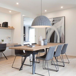 This is an example of a contemporary dining room in Melbourne with white walls, light hardwood floors and beige floor.