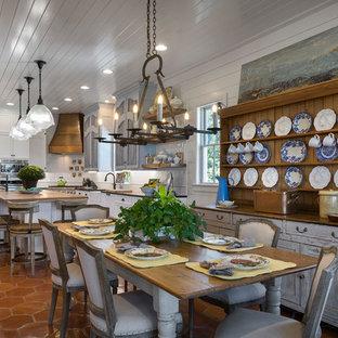 Diseño de comedor de cocina de estilo de casa de campo con paredes blancas, suelo de baldosas de terracota y suelo naranja