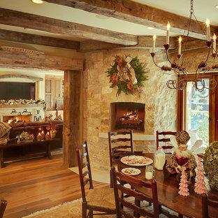 Ejemplo de comedor rústico con suelo de madera en tonos medios, chimenea de esquina y marco de chimenea de piedra