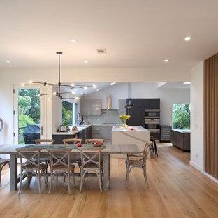 Cette image montre une salle à manger ouverte sur le salon design de taille moyenne avec un mur blanc, un sol en bois clair, aucune cheminée et un sol jaune.