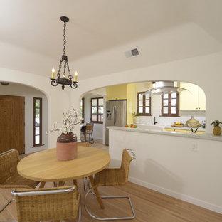 Idee per una sala da pranzo aperta verso la cucina mediterranea di medie dimensioni con pareti bianche e parquet chiaro