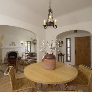 Immagine di una sala da pranzo aperta verso la cucina mediterranea di medie dimensioni con pareti bianche, parquet chiaro, camino classico e cornice del camino piastrellata