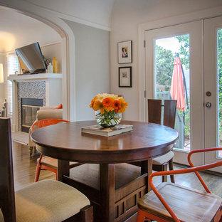 Esempio di una sala da pranzo aperta verso il soggiorno minimal di medie dimensioni con pareti multicolore, parquet scuro, camino classico e cornice del camino in cemento