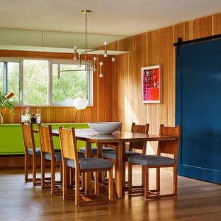Design ideas for a midcentury dining room in Los Angeles with orange walls, medium hardwood flooring and no fireplace.