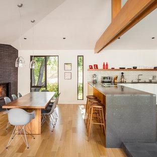 Modelo de comedor nórdico, de tamaño medio, abierto, con paredes blancas, suelo de madera en tonos medios, chimenea de esquina, marco de chimenea de ladrillo y suelo marrón