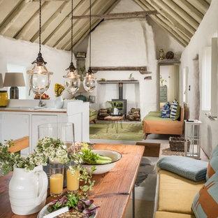 Foto di una sala da pranzo aperta verso il soggiorno rustica con pareti bianche, stufa a legna e pavimento grigio