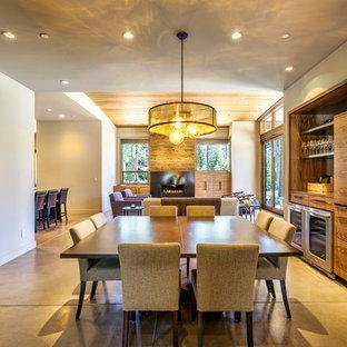 Foto di una sala da pranzo aperta verso la cucina minimal di medie dimensioni con pareti beige, pavimento in cemento, camino classico e cornice del camino in legno