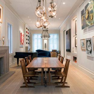 Cette image montre une grand salle à manger design fermée avec un mur blanc, une cheminée standard, un manteau de cheminée en bois et un sol en bois clair.