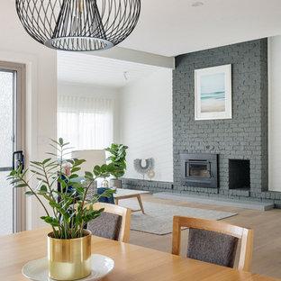 Idee per una grande sala da pranzo aperta verso il soggiorno contemporanea con pareti bianche, pavimento in legno verniciato, stufa a legna, cornice del camino in mattoni e pavimento nero