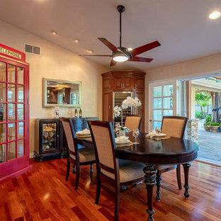 Idee per una sala da pranzo aperta verso la cucina tradizionale di medie dimensioni con pareti beige, pavimento in legno massello medio, camino bifacciale, cornice del camino in intonaco e pavimento marrone