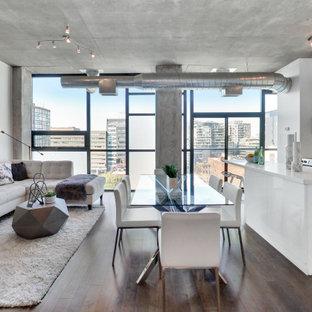 Immagine di una sala da pranzo aperta verso la cucina industriale con pareti bianche, parquet scuro e pavimento marrone