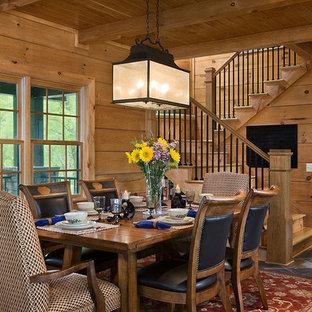Ispirazione per una sala da pranzo aperta verso il soggiorno stile rurale di medie dimensioni con pareti marroni, pavimento in ardesia e nessun camino