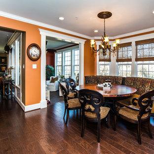 Exemple d'une salle à manger ouverte sur la cuisine chic de taille moyenne avec un mur orange, un sol en bois foncé, aucune cheminée et un sol marron.