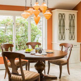 Cette photo montre une salle à manger ouverte sur la cuisine chic avec un mur orange, aucune cheminée et un sol en travertin.