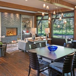 Inspiration för mycket stora klassiska matplatser med öppen planlösning, med mellanmörkt trägolv, en standard öppen spis, en spiselkrans i sten och grå väggar