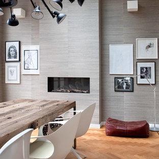 На фото: столовая в современном стиле с серыми стенами и горизонтальным камином с