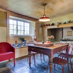 Immagine di una sala da pranzo aperta verso la cucina shabby-chic style di medie dimensioni con pavimento in pietra calcarea e pavimento nero