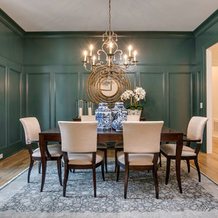 This is an example of a traditional separate dining room in Raleigh with medium hardwood floors, brown floor and green walls.