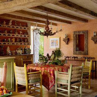 Immagine di una sala da pranzo aperta verso la cucina mediterranea con pareti arancioni
