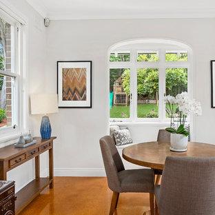 シドニーの大きいトランジショナルスタイルのおしゃれなダイニングキッチン (コルクフローリング、コーナー設置型暖炉、漆喰の暖炉まわり、オレンジの床、白い壁) の写真